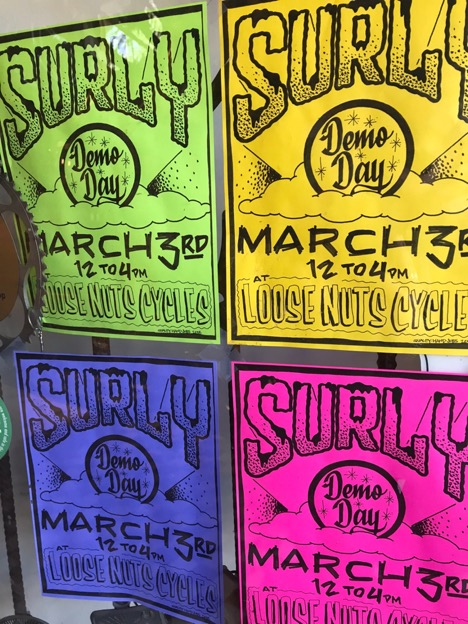 Four different colored Surly demo day fliers taped to a glass window