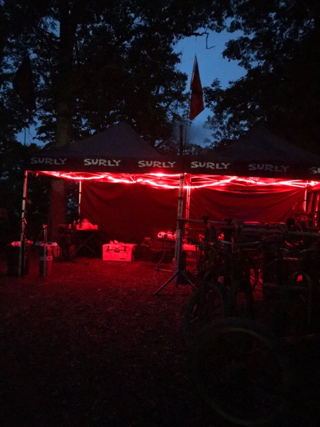 Two Surly pop up canopies with red string lights lit up in front at night in the woods