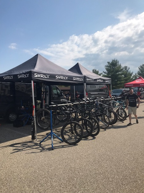 Bikes line up in front of two Surly pop up canopies on a paved lot