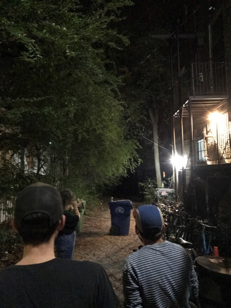 Three people standing next to a building at night looking into the trees