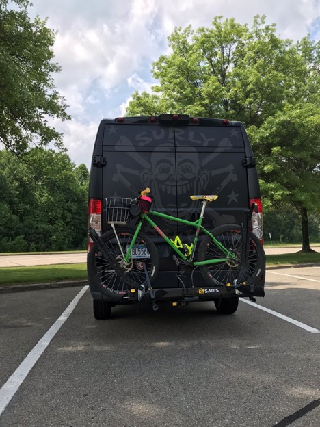 Surly bike,green, mounted on the rear of a black van in a parking lot with trees in front