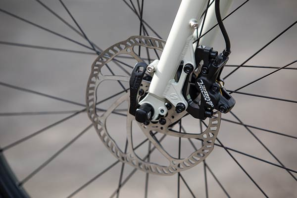 Zoom in of the front brake disc and caliper on the fork of a Surly Big Easy bike