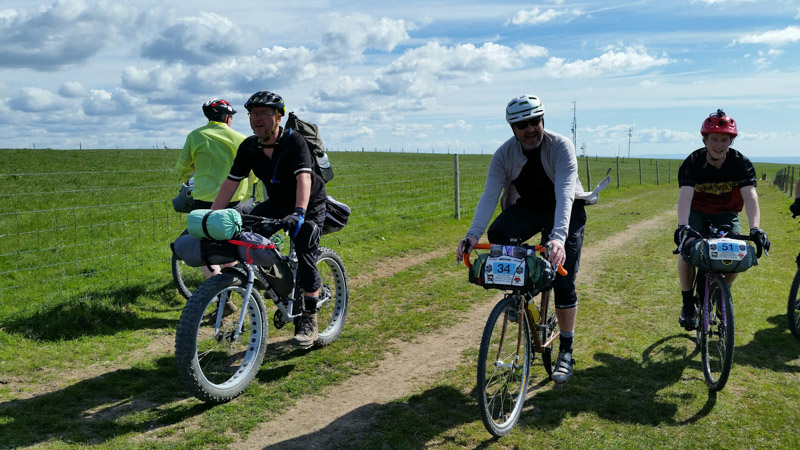 Front view of cyclists, side by side, riding down a pasture road, alongside a wire fence
