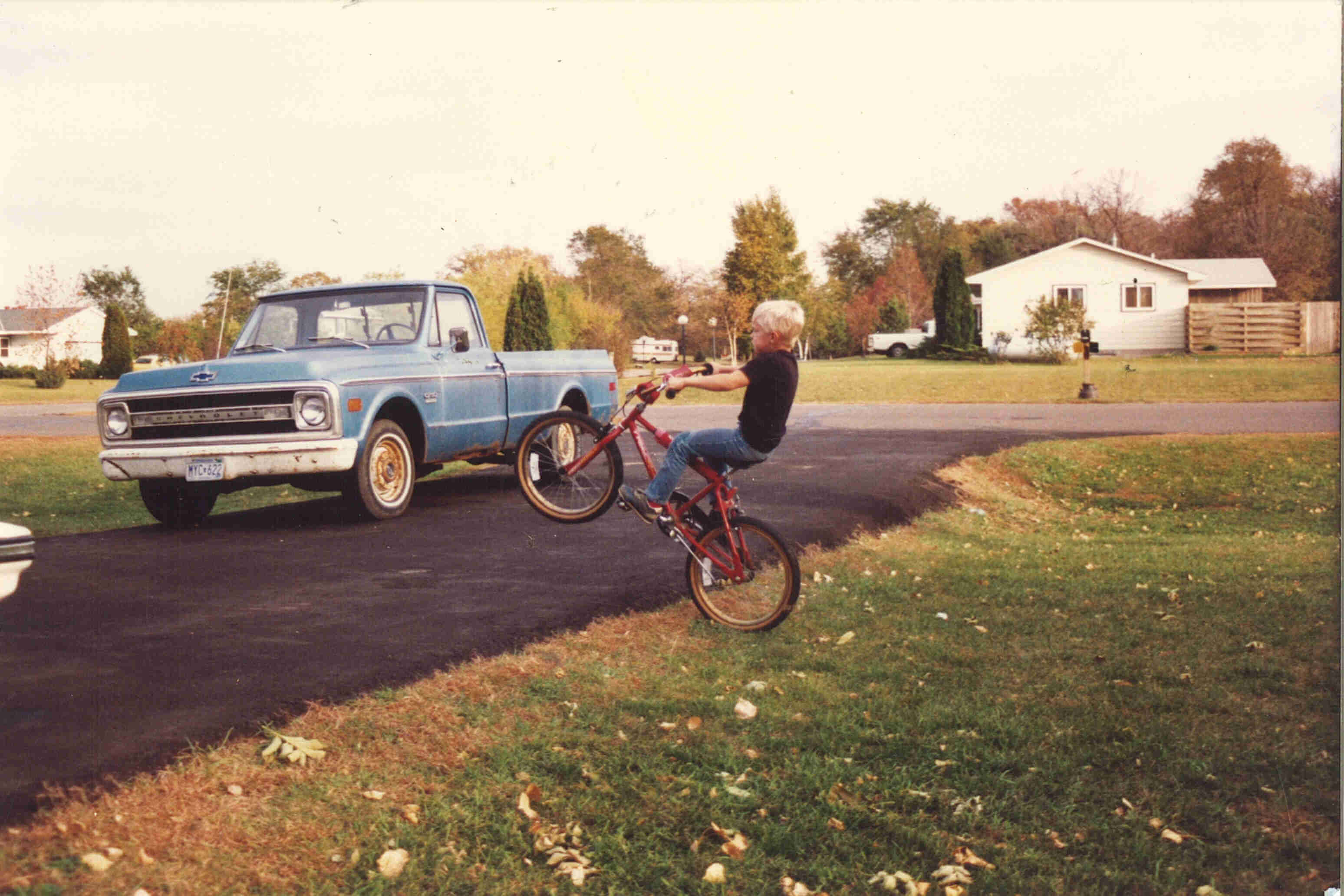 Left side view of a child riding a wheelie on a red BMX bike, next to a driveway with a blue truck parked on it