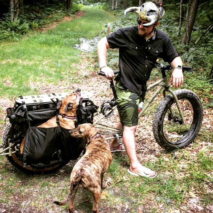 Cyclist stands with a Surly Big Fat Dummy bike with a dog in rear saddle bag and a second dog standing on a grass trail