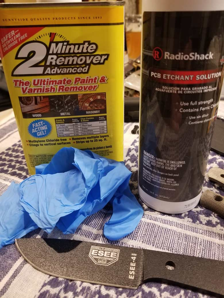 Can of paint and varnish remover, bottle of PCB etchant solution, black knife blade and nitrile gloves on woven blanket