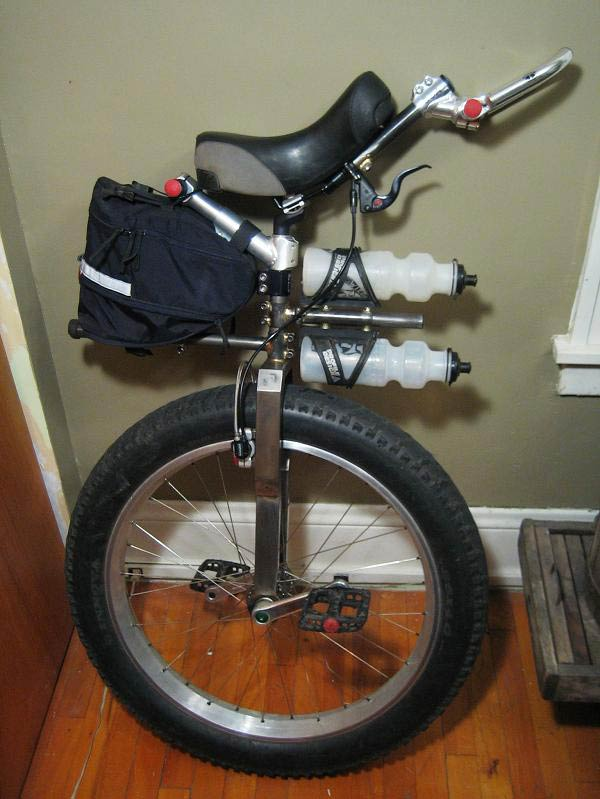Right side view of a fat wheeled unicycle, parked in a room with wood floors, next to a wall