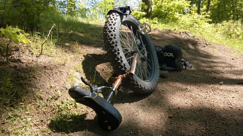 A unicycle with a fat bike wheel, laying down on a dirt trail in the woods