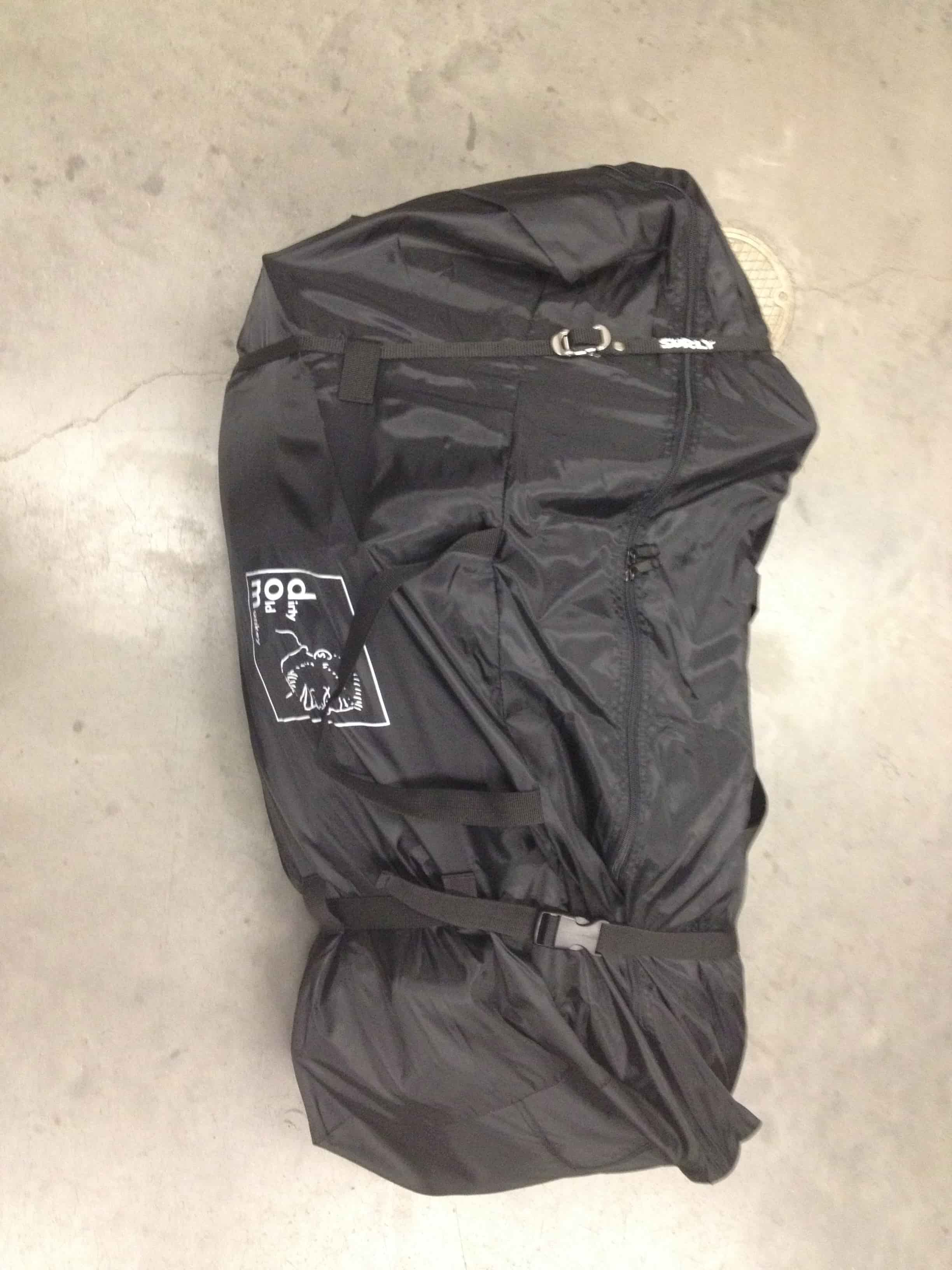 Downward view of a zipped up, black gear bag, with a Surly Junk Strap wrapped around it, on a cement floor