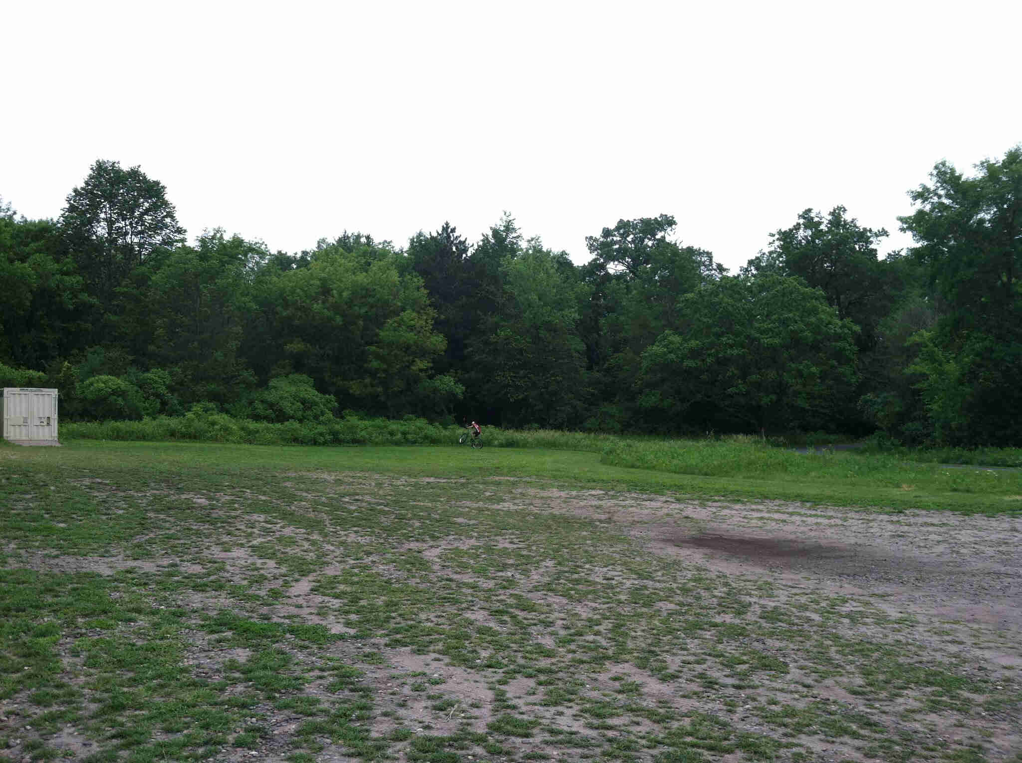 A dirt and grass field with a cyclist in the distance, riding a Surly Krampus bike across a tree line