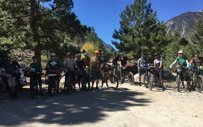 Group of cyclist lined up on a gravel patch in front of pines with mountain in the background