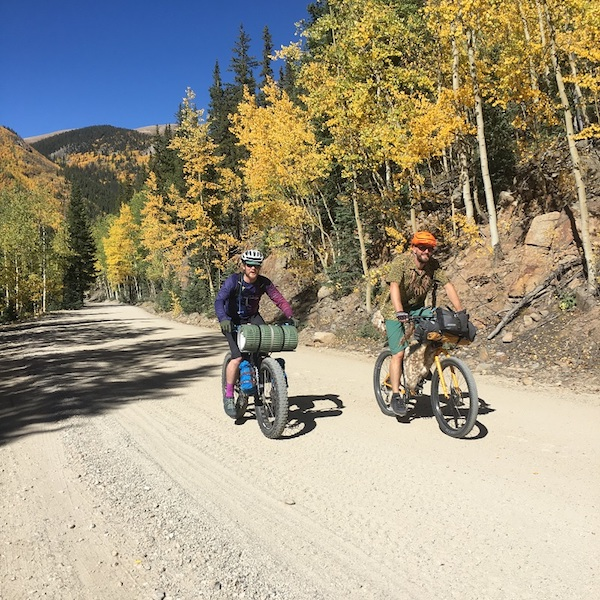 Two cyclist ride up a gravel road hill with yellow leafed trees, mountain hills and blue sky in the backgound