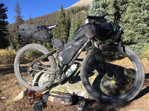 Surly bike loaded with gear leans on a rock with pine trees and a mountain hill in the background