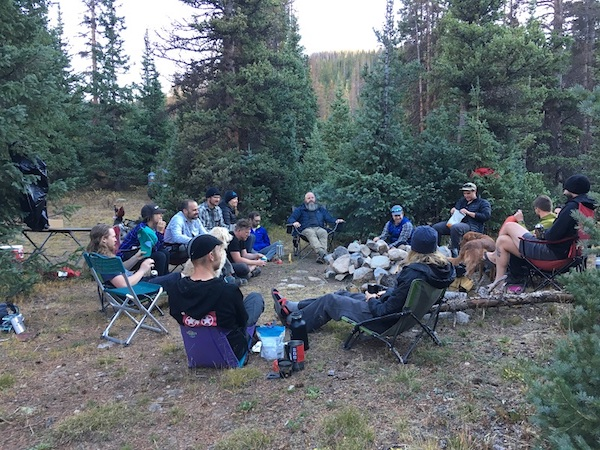 Group of people sitting in folding chairs in a circle inside of clearing surrounded by pine trees