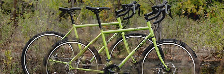 Right side view of 2, pea lime soup colored, Surly Disc Trucker bikes, side by side, on watery ground with brush behind