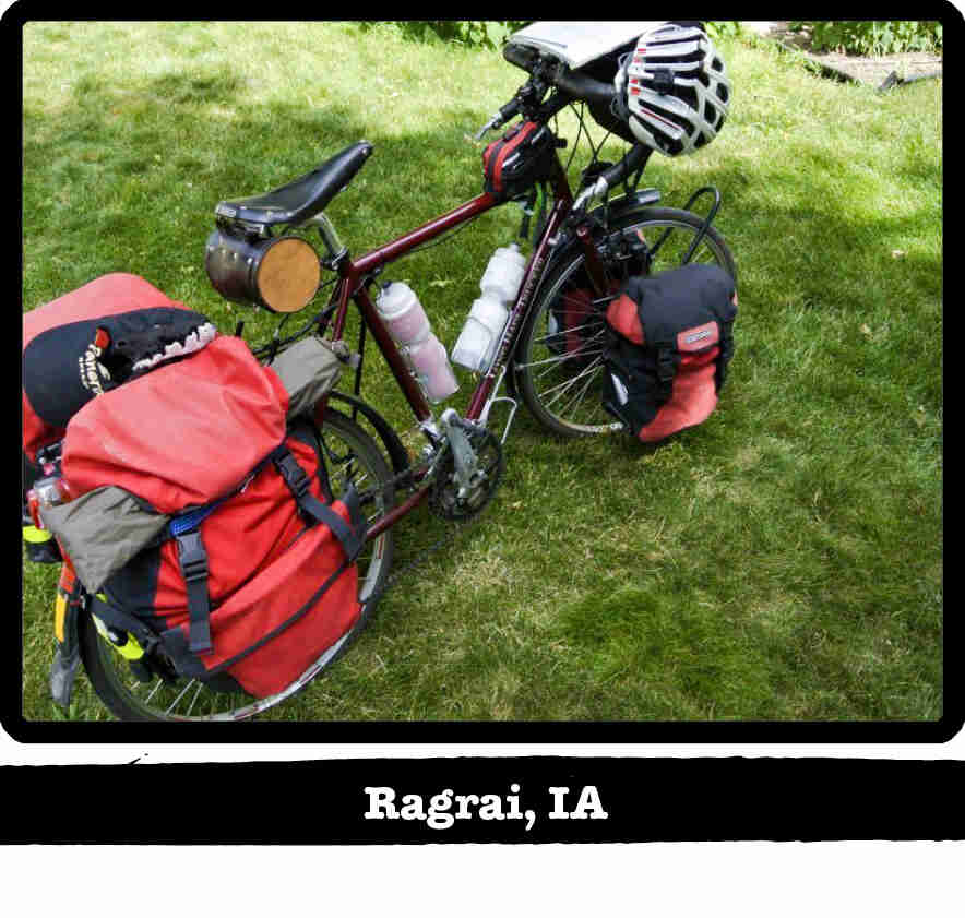 Right side view of a dark red Surly Long Haul Trucker bike, loaded with gear, on grass -Ragbrai, IA tag below image