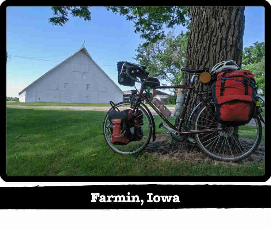Left profile of a Surly Long Haul Trucker bike, tan, leaning on a tree on a farm - Farmin, IA tag below image