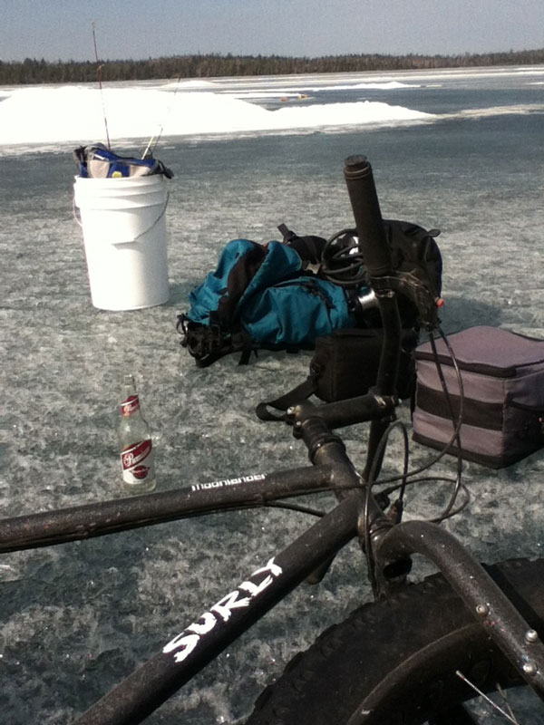 Right side view of a Surly Moonlander fat bike, laying on a frozen lake, next to ice fishing gear and a beer bottle