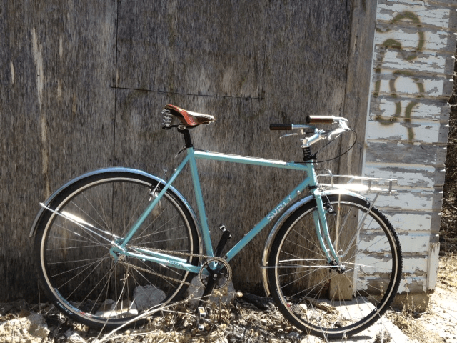 Right side view of a light blue Surly bike, leaning on an exterior, plywood wall