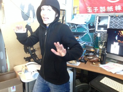 Front view of a person wear a black Surly Hoodie for woman, standing in front of a desk in an office