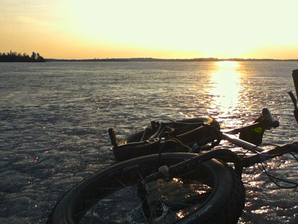 Front, right side view of a Surly Moonlander fat bike, laying on a frozen lake at sunset