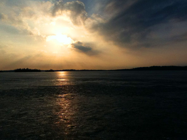 A frozen lake at sunset with clouds in the sky