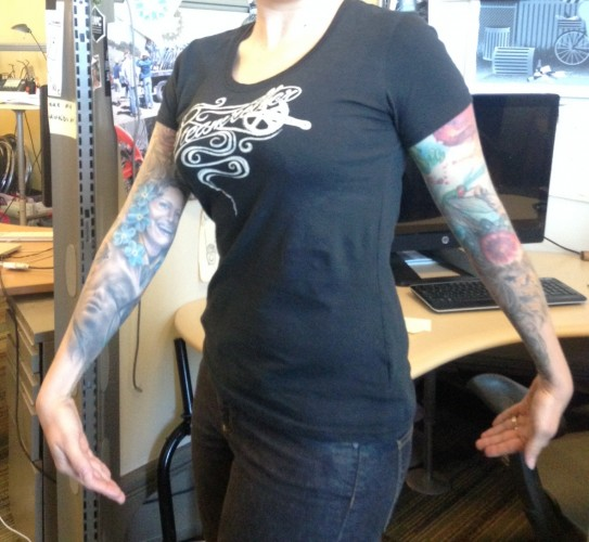 Front view of a person wearing a black Surly Steamroller, women's t-shirt, in front of a desk in an office