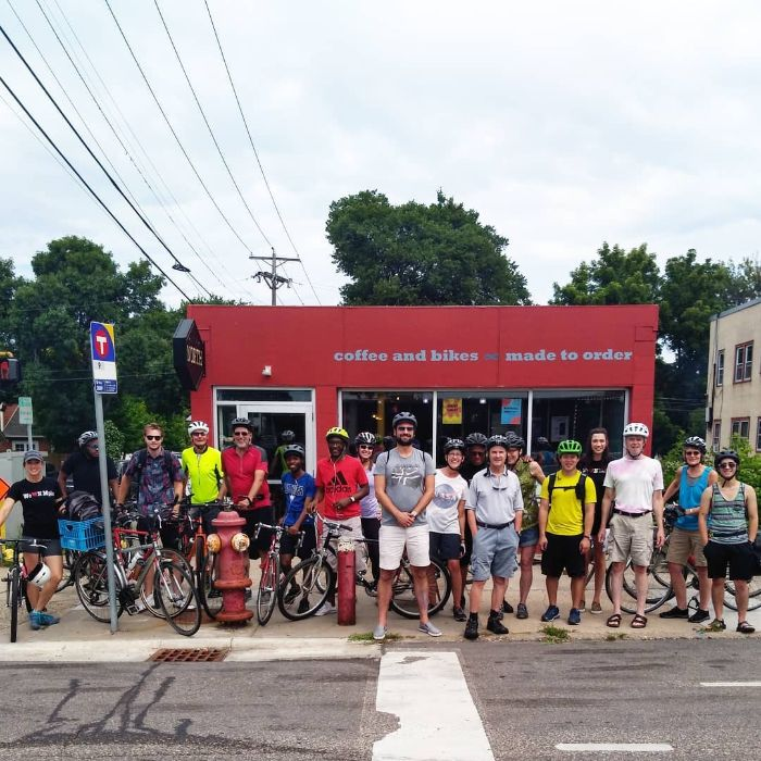 A group of cyclist stand in front red bike shop with their bicycles