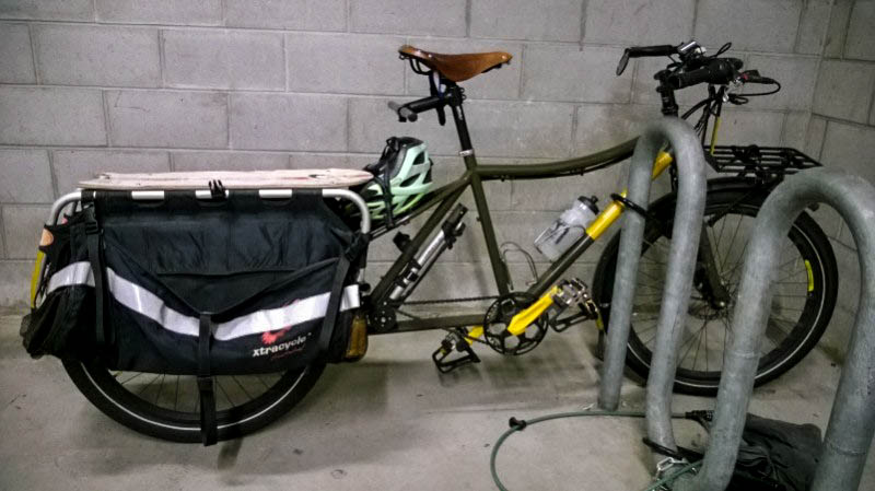 Right side view of an olive color Surly Big Dummy bike, parked against a bike rack next to cinder block walls