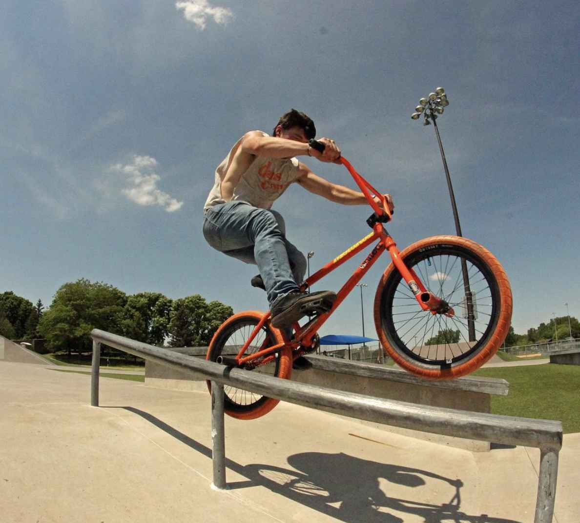 Person riding an orange BMX bike balances on the right rear axle peg down a steel rail at a rec park on a sunny day