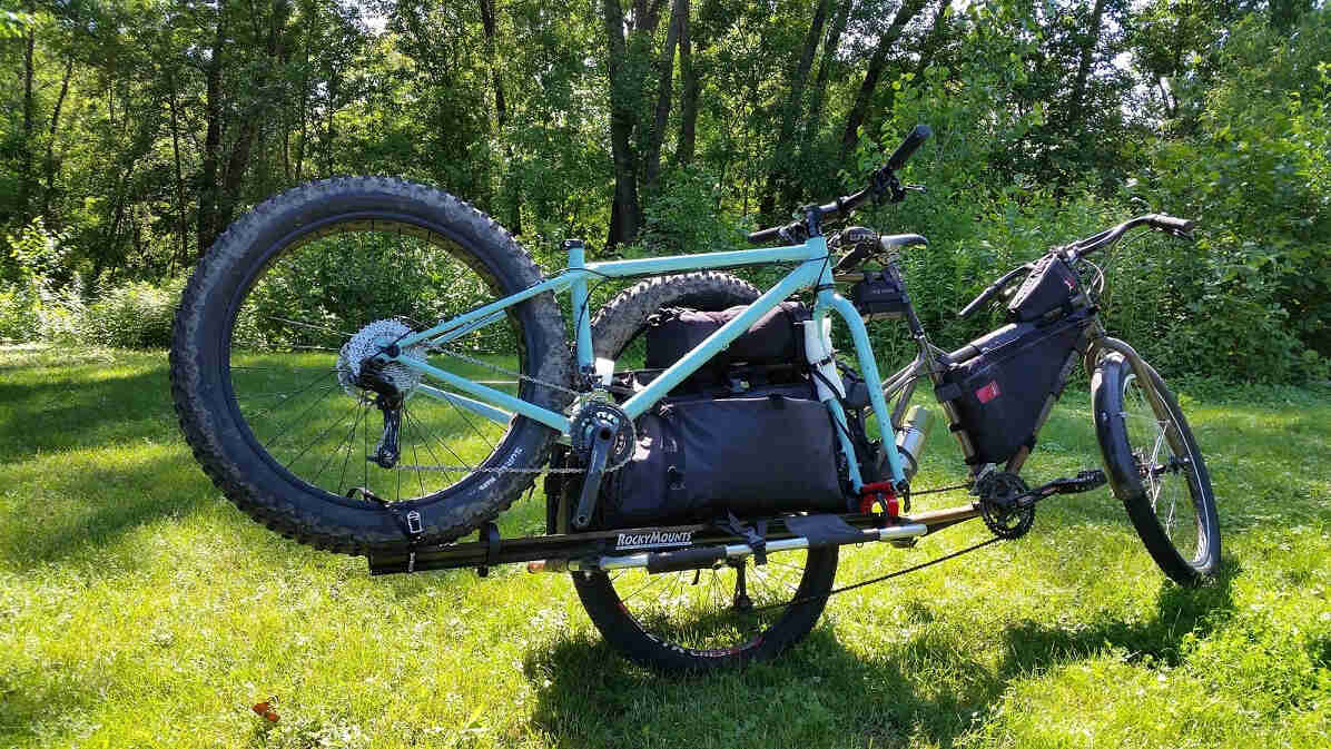 Rear, right side view of a Surly Big Dummy bike hauling a fat bike, parked in a grass field in front of trees