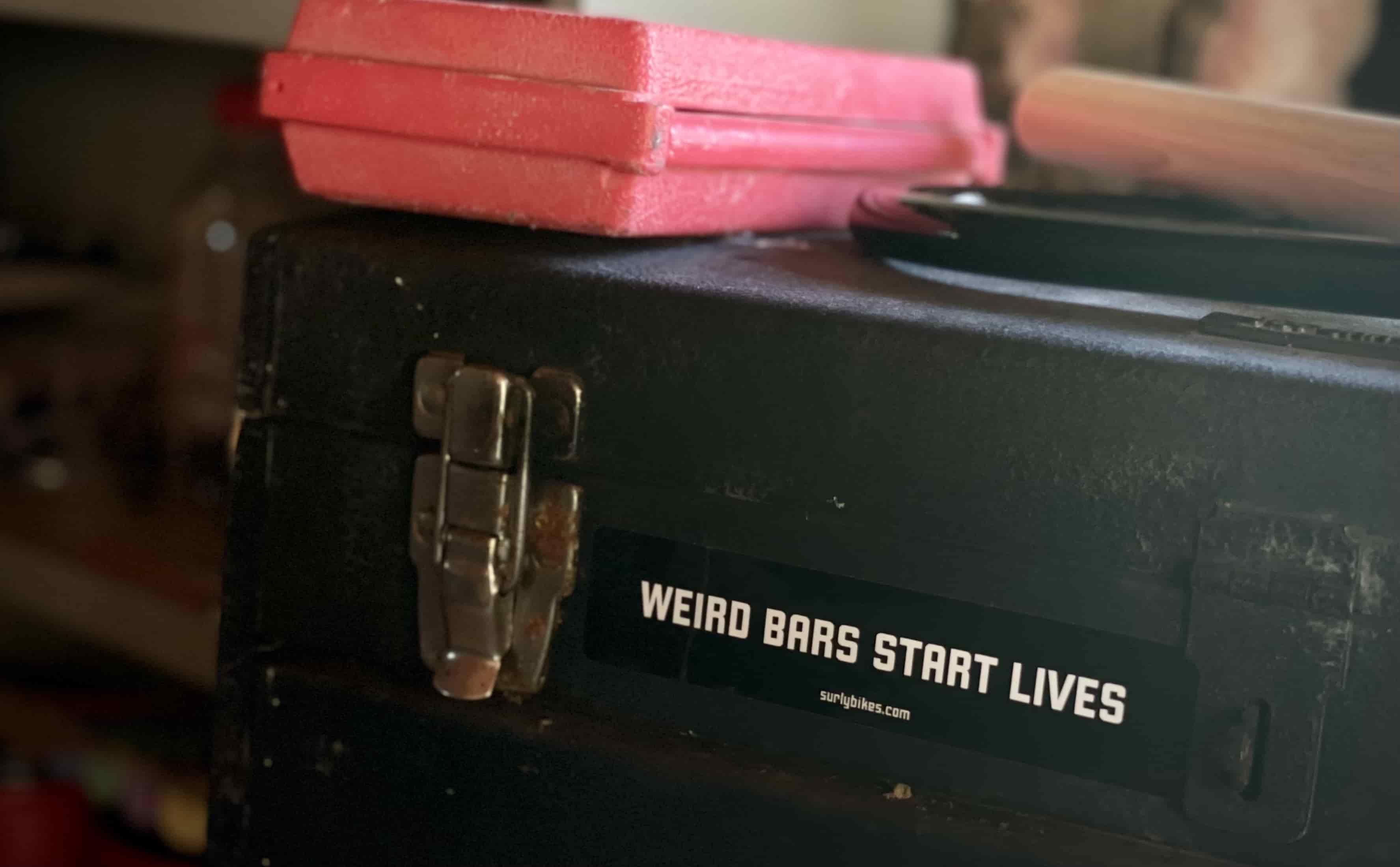 """Black sticker on toolbox that says, """"weird bars start lives"""""""