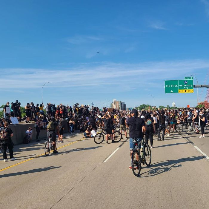 A group of pedestrians and cyclists gather on the I-35 freeway bridge in Minneapolis