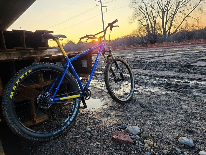 A blue colored Surly bike leans on a stack of steel beams on a muddy patch of land with the sun on the horizon