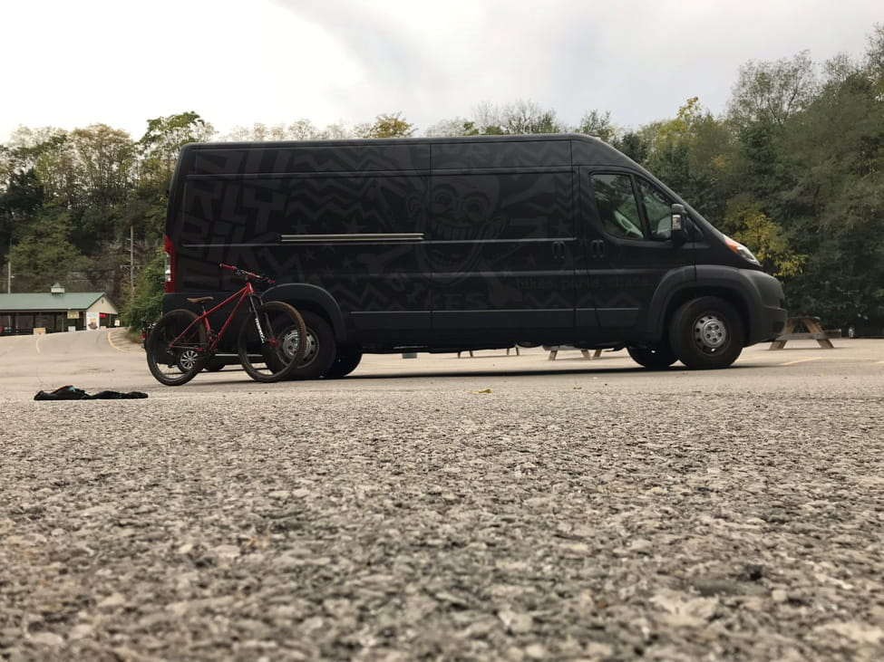 Right side view of a red bike leaning on a rear wheel well of a black Surly van, at a parking with trees behind