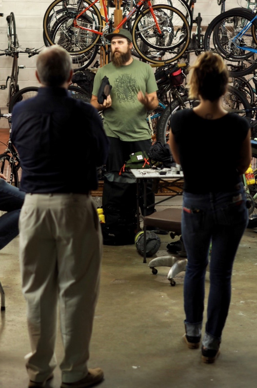 The backsides of 2 people listening to a person to a person facing them with bikes hanging from racks in the background