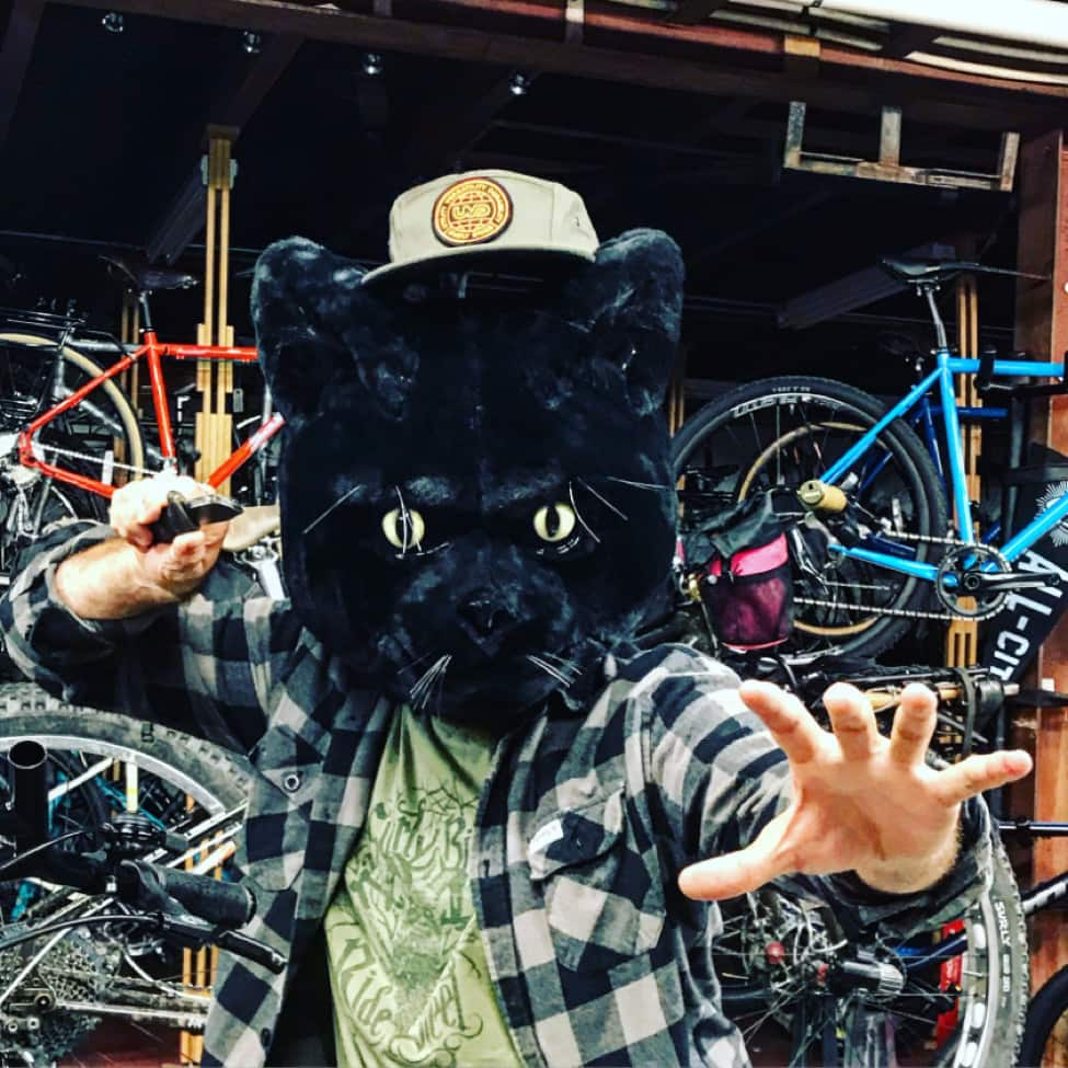 Front view of person in a karate pose, wearing a large black panther head, in front of a garage with bikes around