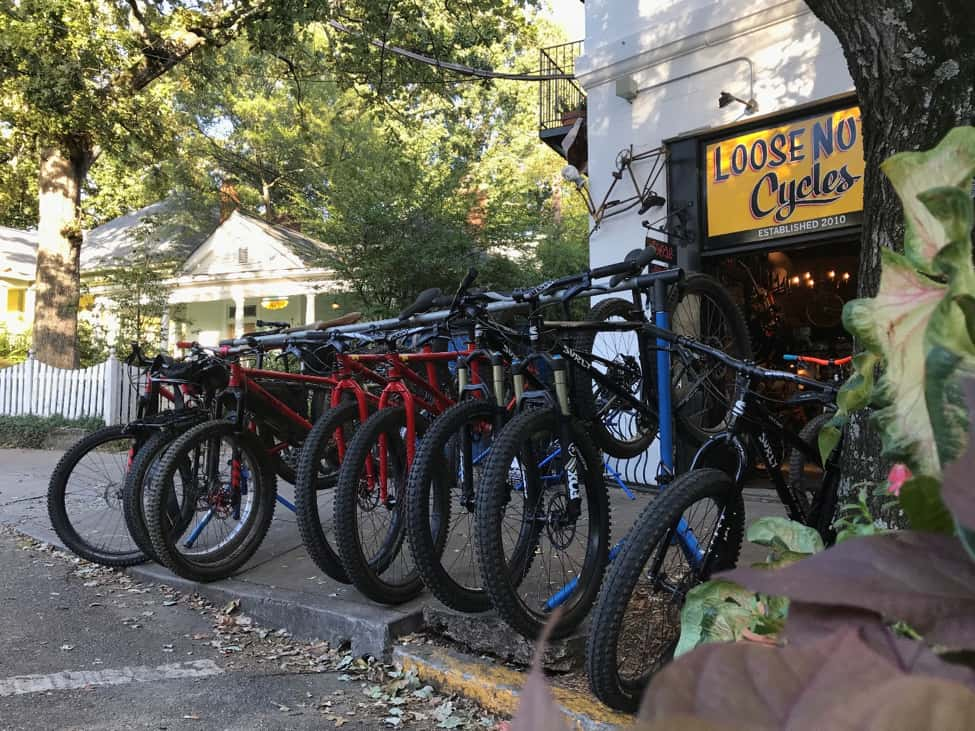 Bikes lined up side by side in a rack, on a sidewalk, with the Loose Nuts bike shop in the background