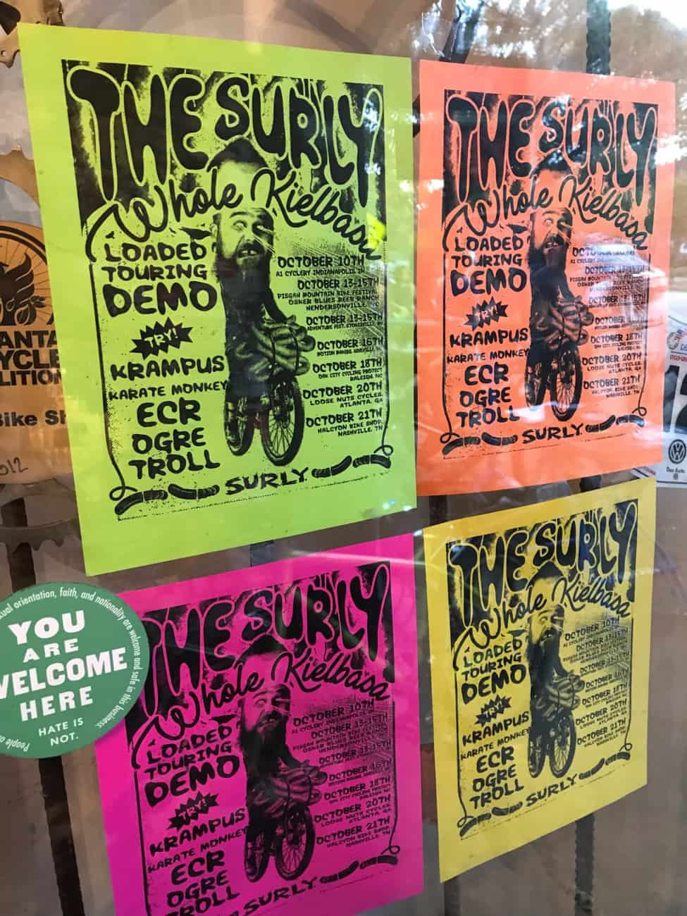 Four colorful 'The Surly Whole Kielbasa', flyers taped to a store front window
