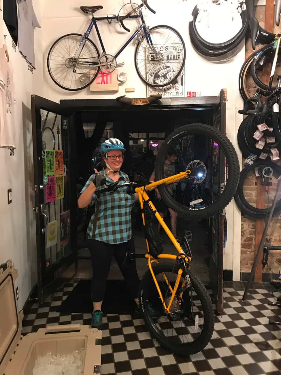 Front view of a cyclist giving a thumbs up at a bike shop, while holding a bike with front wheel popped off the ground