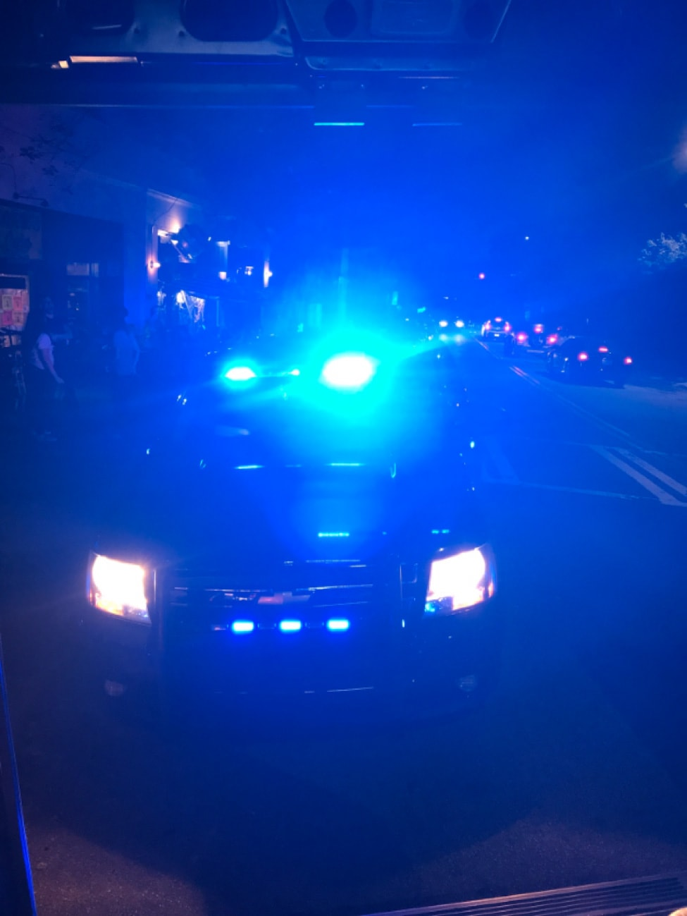 Front view of a police car on the street with it's light on at night