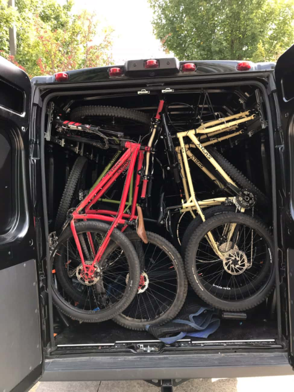 Rear view of a van with the rear doors open, showing Surly bikes packed in, seat to seat, from top to bottom