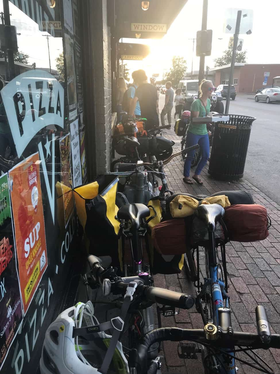 Bikes lined up and parked on a red brick sidewalk, next to the window of a pizza shop
