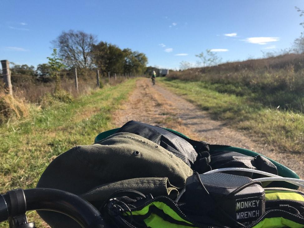 View from the top of a bike handlebar gear pack, facing down a country gravel road  with thick grass to the sides of it