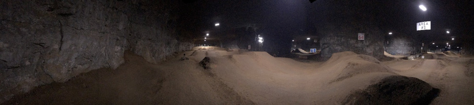 A dirt bike race track inside of a large cavern with lights above