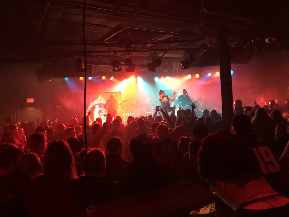 View from the back of a dark room facing a lighted stage with a band performing for a large group of people