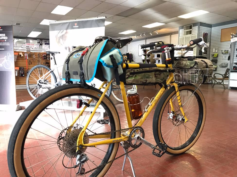 Right side angled view of a yellow Surly bike with gear, on the red brick floor of a bike shop showroom