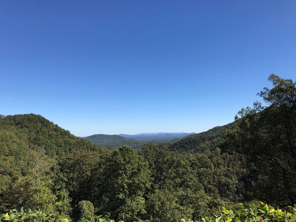 Green leafed trees completely cover a valley with hills on a clear blue sky day at Kitsuma Peak
