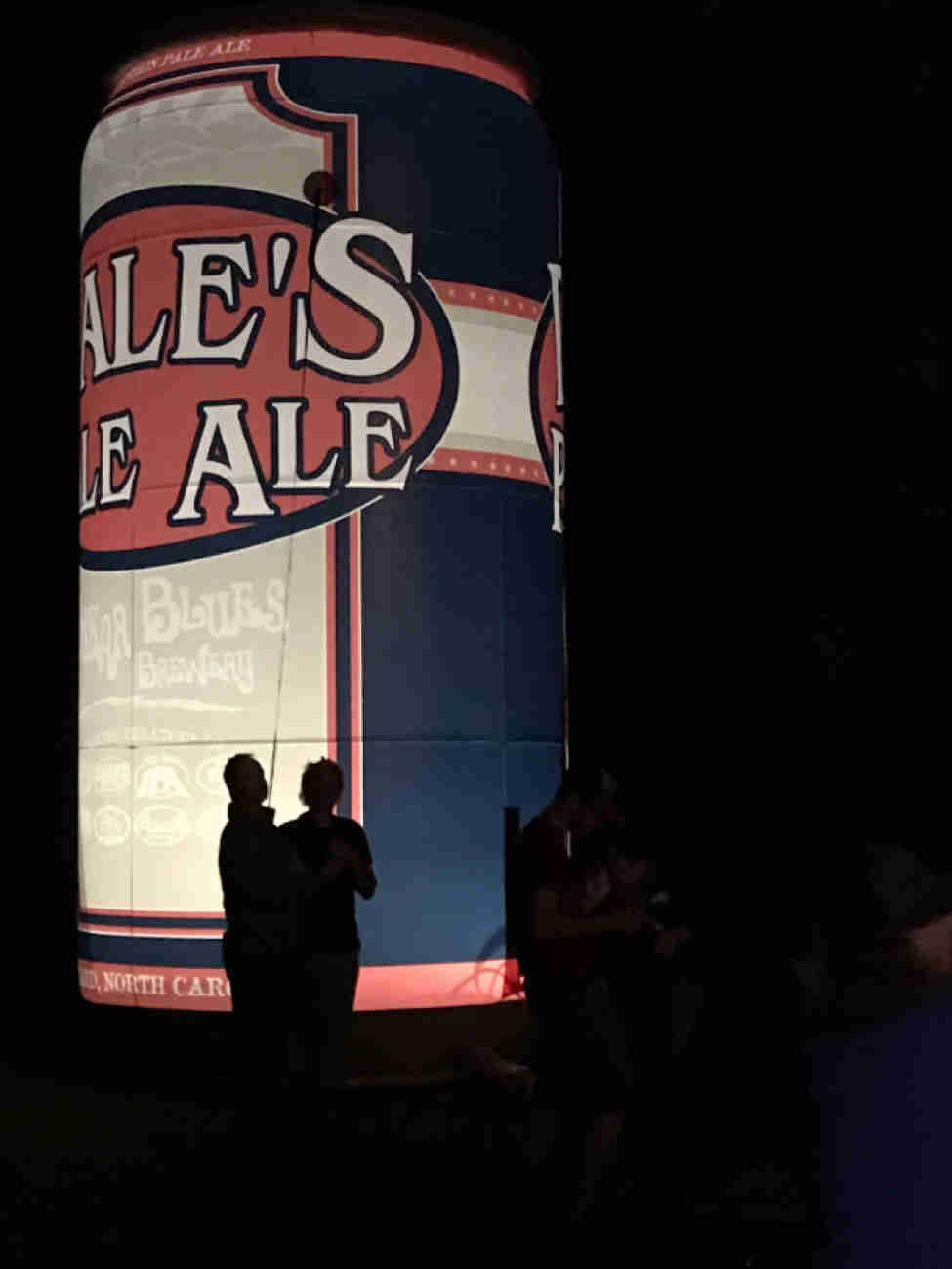 Silhouettes of people standing in front of a large, lighted inflatable beer can at night