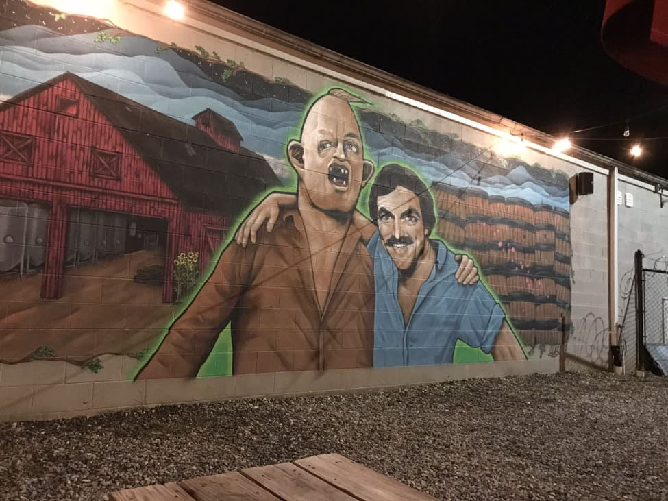 Nighttime view of a mural on a wall showing Lar, from Goonies, and Tom Selleck with their arms on each others shoulders